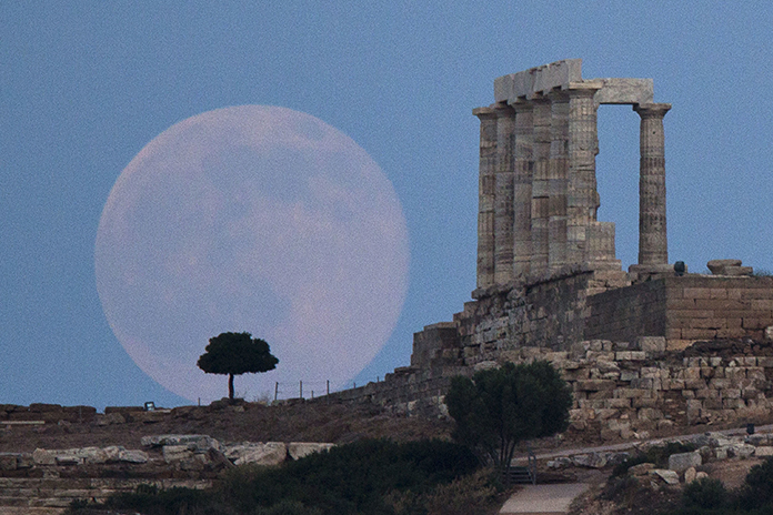 In this June 20, 2016 file photo, the full moon rises behind a tree next to the ruins of the ancient marble Temple of Poseidon, built in 444 BC, at Cape Sounion, southeast of Athens, on the eve of the summer solstice. A California-led research team reported that the moon formed within 60 million years of the birth of the solar system. (AP Photo/Petros Giannakouris)