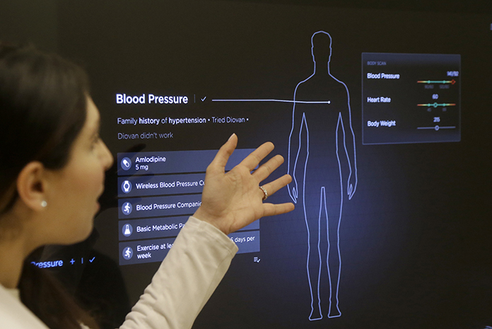 In this Jan. 10, 2017 photo, Dr. Aaliya Yaqub points to a large monitor while giving a demonstration of medical checkup at a Forward medical office in San Francisco. (AP Photo/Jeff Chiu)