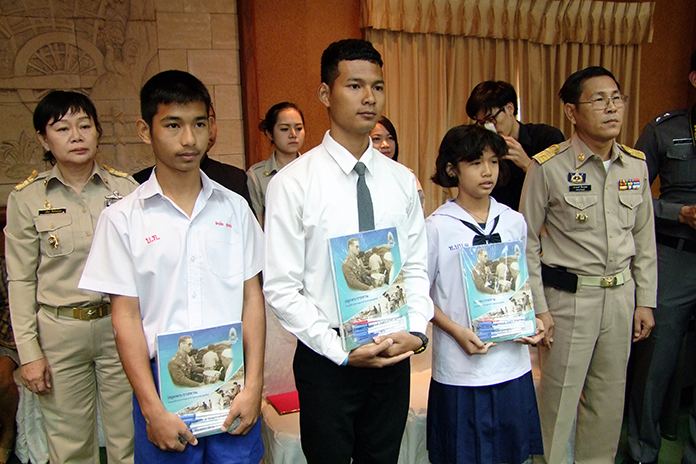 Jedsada Promsri, Akarachai Sukhuang, and Pornpravee Sukhuang receive scholarships from a royally backed foundation sympathetic to the needs of flood victims.