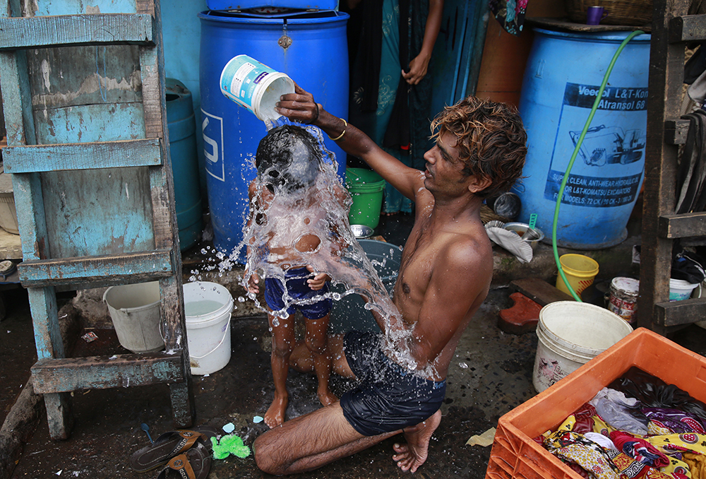 In this May 23, 2016, file photo, a man bathes his son on a hot afternoon in a slum in Mumbai, India. For the third straight year, Earth set a record for the hottest year, NOAA and NASA announced. NASA says 2016 was warmer than 2015 - by a lot. It's mostly global warming with a little assist from the now-gone El Nino. (AP Photo/Rafiq Maqbool, File)