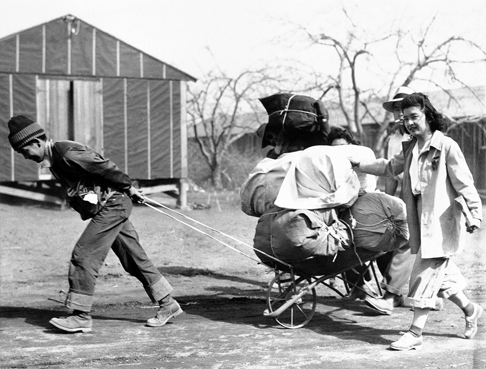 In this June 19, 1942 file photo, Japanese evacuees move into a war relocation authority center in Manzanar, Calif. Roughly 120,000 Japanese immigrants and Japanese-Americans were sent to desolate camps that dotted the West because the government claimed they might plot against the U.S. (AP Photo/File)