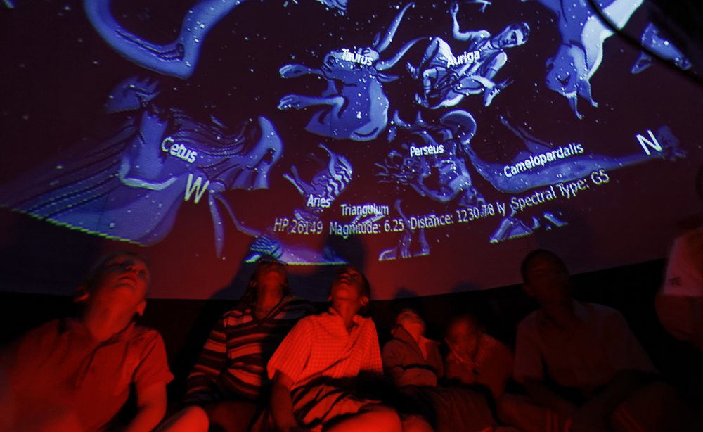 Students look up at a projected display inside an inflatable planetarium, during a visit by The Traveling Telescope to show students the science of astronomy, at St Andrew's School near Molo in Kenya's Rift Valley. (AP Photo/Ben Curtis)