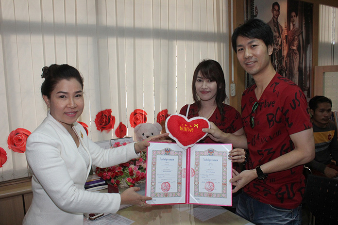 Miss Ampon Deboaw, Banglamung Bailiff, shown here after writing a legal marriage certificate for a Thai-Japanese couple, also was busy giving out matching love pillows.