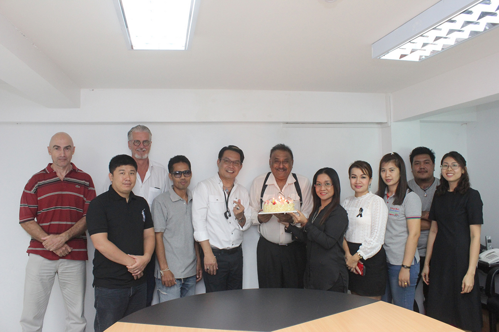 A small group of the Pattaya Mail family gather around to sing happy birthday to the chief.