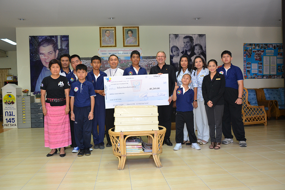 General Manager Andre Brulhart presents a check for 40,269 baht to Father Ray Vice President Rev. Pattarapong Srivorakul Feb. 21.