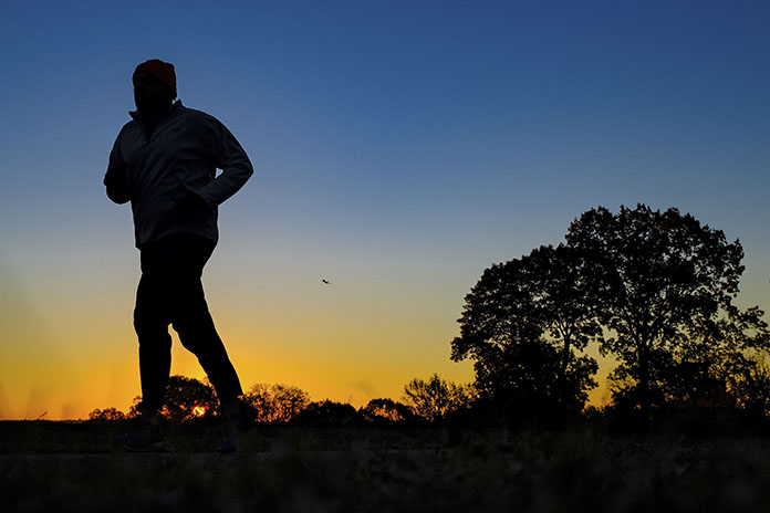 A runner is silhouetted against the sunrise on his early morning workout near Arlington National Cemetery in Arlington, Va., across the Potomac River from the nation's capital. Research released on Monday, Jan. 9, 2017 suggests that people who pack their workouts into one or two days a week lower their risk of dying as much as those who exercise more often, as long as they get enough of it. (AP Photo/J. David Ake)