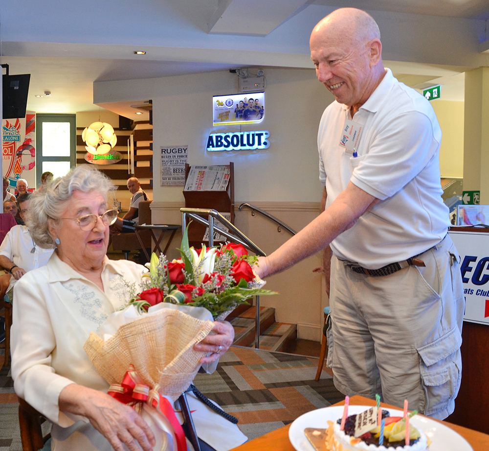 Governing Board Chairman Roy Albiston presents Marjorie Blissett with a bouquet of roses in celebration of her upcoming 90th birthday and for her continued contributions to the Pattaya City Expats Club over the years.