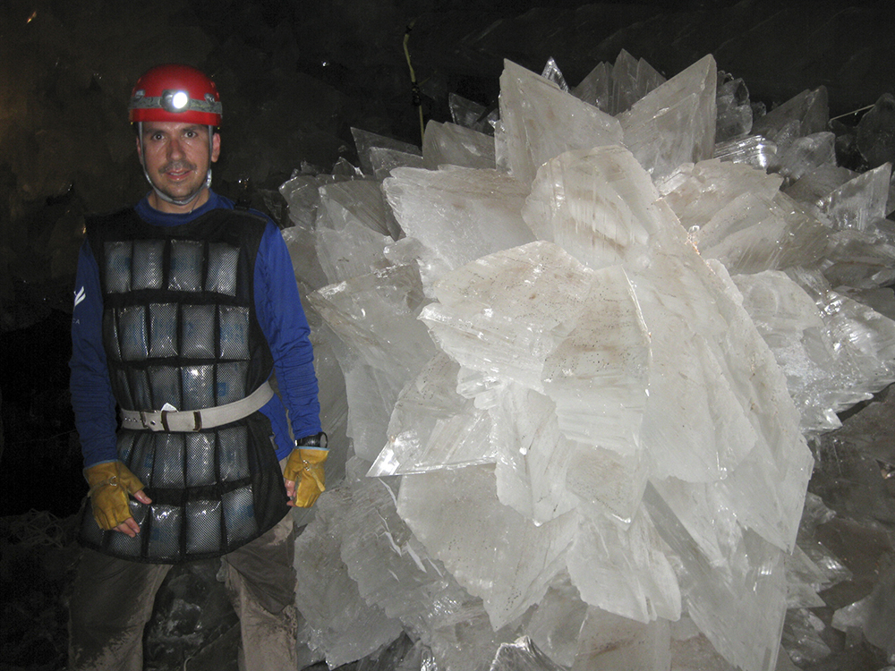 Mario Corsalini stands near to a gypsum rosette crystal. In a Mexican cave system so beautiful and hot that it is called both Fairyland and hell, scientists have discovered life trapped in crystals that could be 50,000 years old. (Mike Spilde via AP)