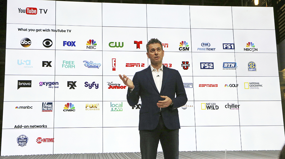 Chief Business Officer Robert Kuncl, with a graphic showing the many networks that will be carried, speaks during the introduction of YouTube TV at YouTube Space LA in Los Angeles. (AP Photo/Reed Saxon)