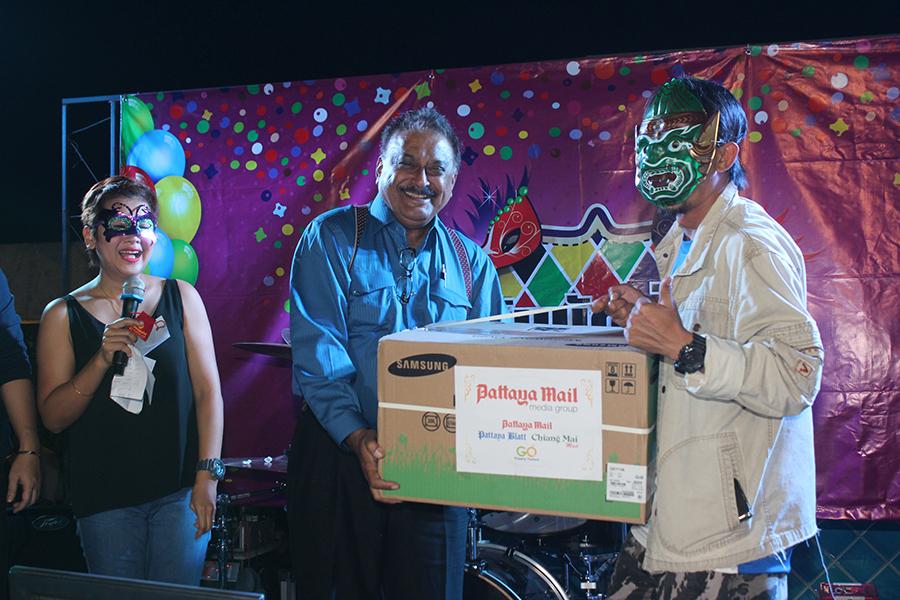 Pratheep Malhotra presents a raffle prize to journalist Teerarak Suthathiwong.