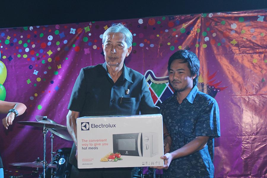 Saksit Yaemsri presents a prize to Tiwakorn Kritmanee.