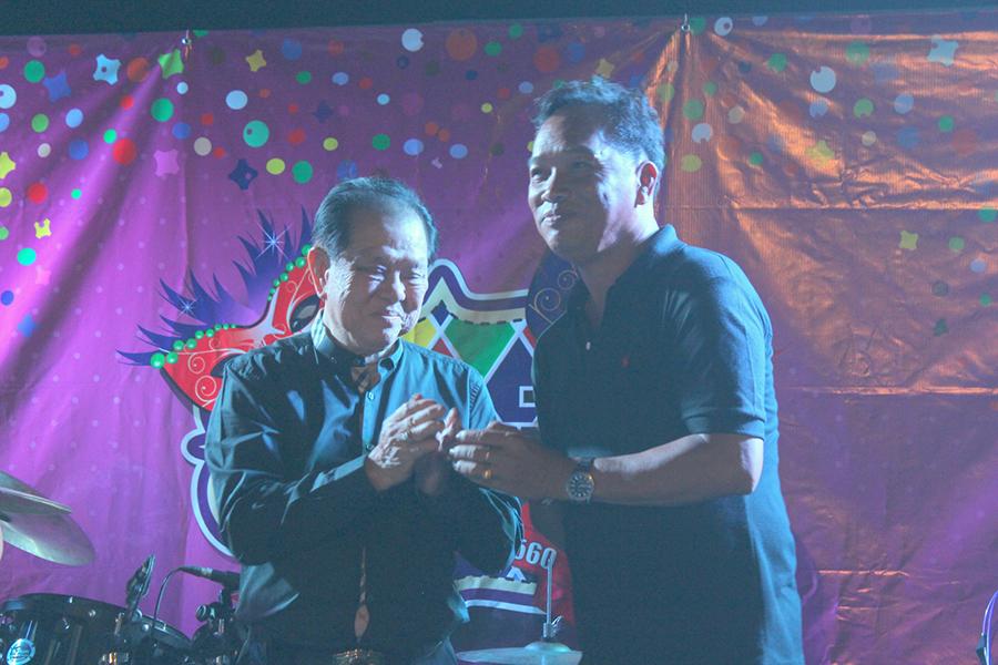Dr. Santsak Ngampichet presents a gold chain to Anan Sukhwattana.