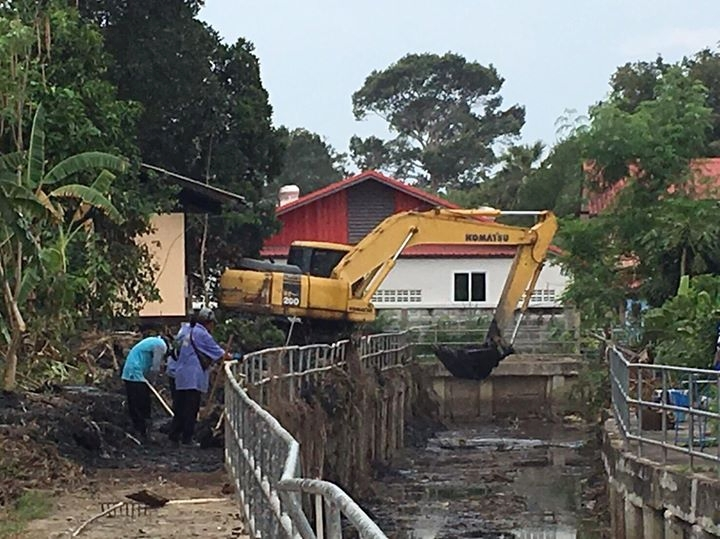 A team of workers with a backhoe dredge weeds and garbage from Naklua's Nokyang Canal.