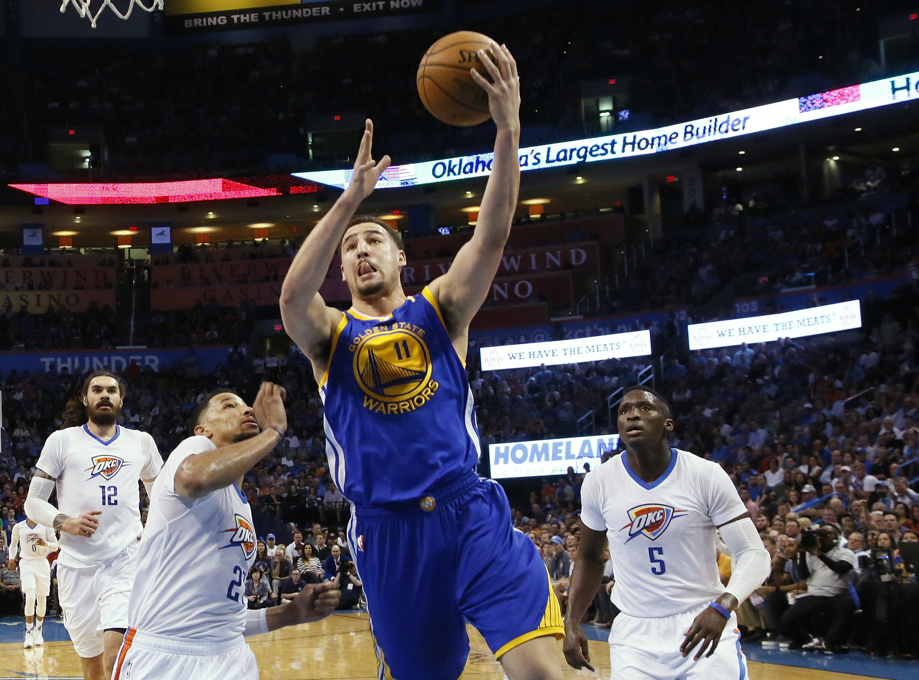 Golden State Warriors guard Klay Thompson (11) shoots between Oklahoma City Thunder forward Andre Roberson (21) and guard Victor Oladipo (5) during the first quarter of their NBA basketball game in Oklahoma City, Monday, March 20. (AP Photo/Sue Ogrocki)