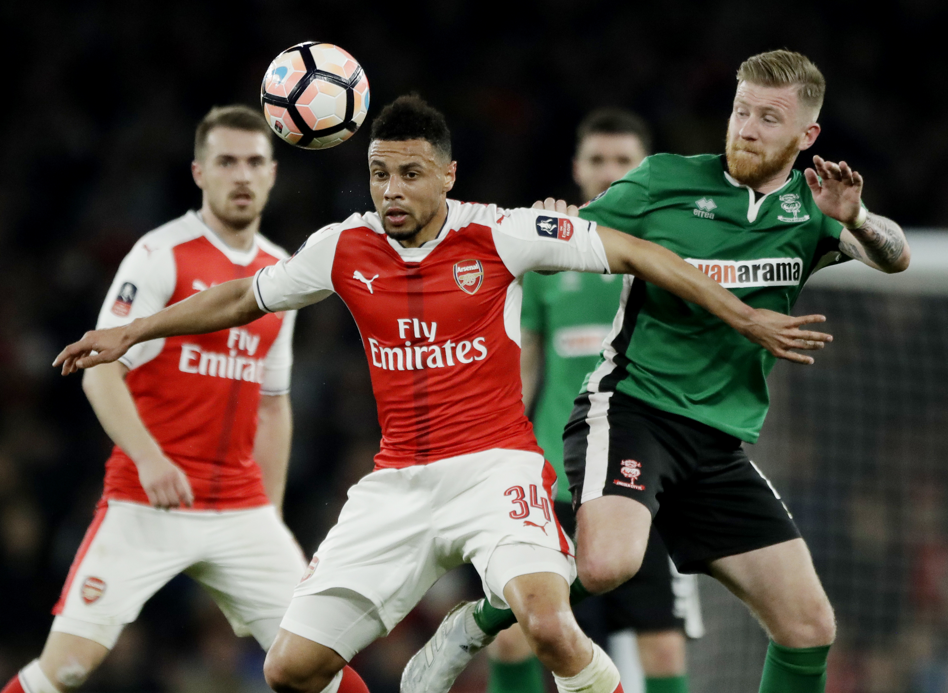 Arsenal's Francis Coquelin competes for the ball with Lincoln City's Alan Power, right, during their English FA Cup quarterfinal match at the Emirates stadium in London, Saturday, March 11. (AP Photo/Matt Dunham)