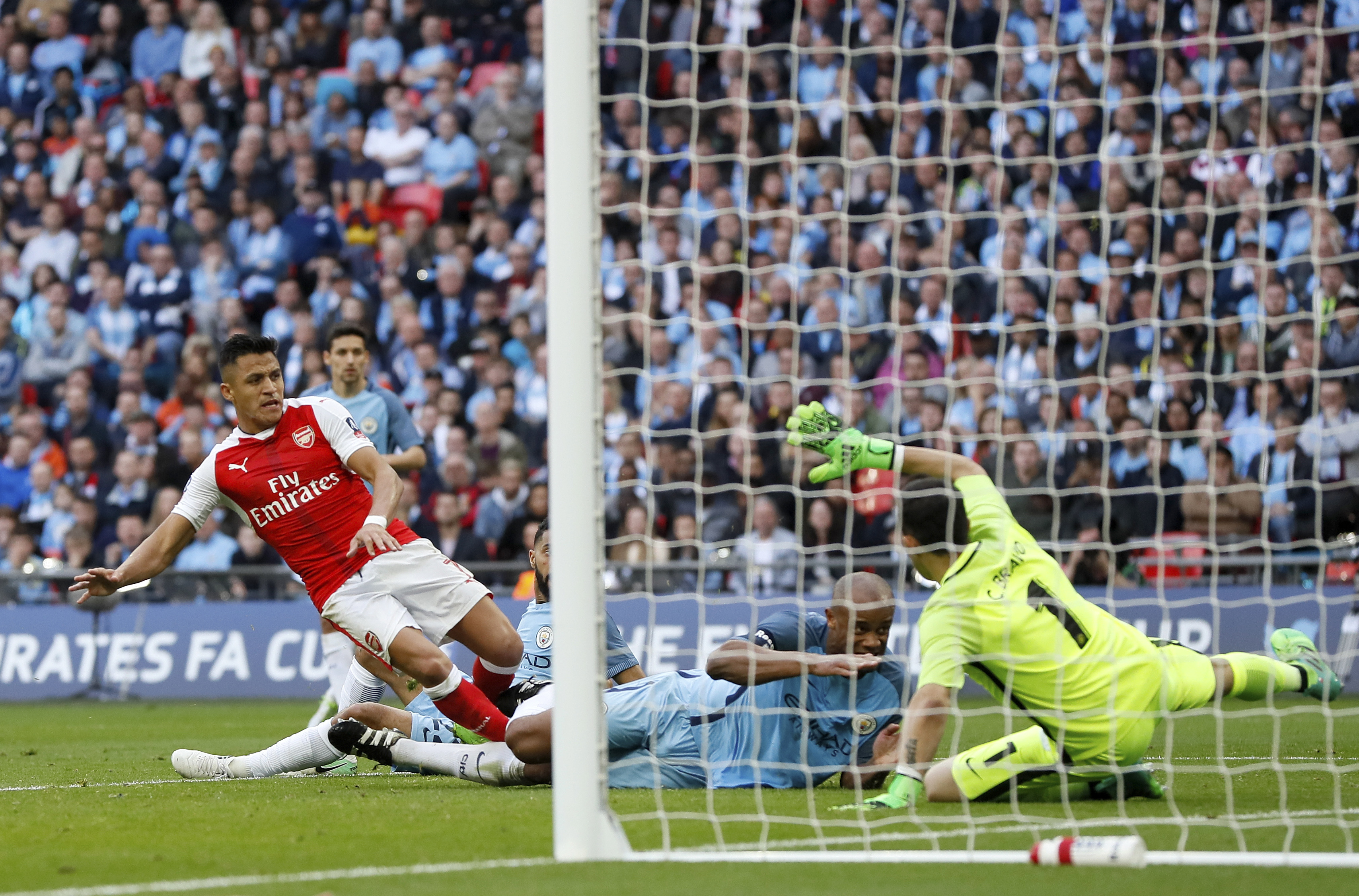 Arsenal's Alexis Sanchez, left, scores his side's second goal past Manchester City goalkeeper Claudio Bravo, right, during their English FA Cup semifinal at Wembley stadium in London, Sunday, April 23. (AP Photo/Kirsty Wigglesworth)