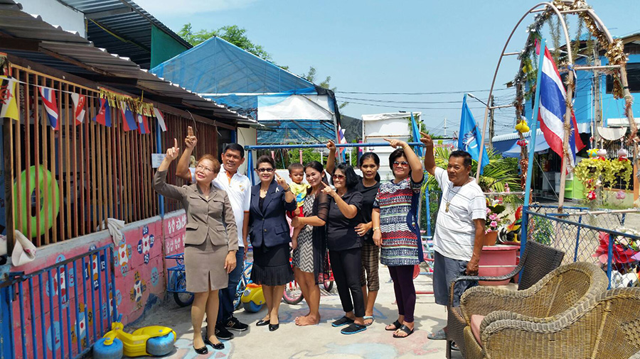 Janta Airmic presents 5,000 baht to daycare center director Kantana Ponchai to help finish the roof on the Soi Korphai Community's children's center.