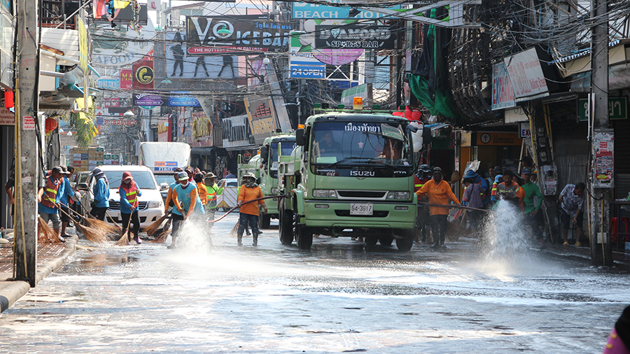 A water truck hoses down the street while workers sweep away dirt and garbage to give Walking Street a good scrubbing before next week's Songkran party begins.