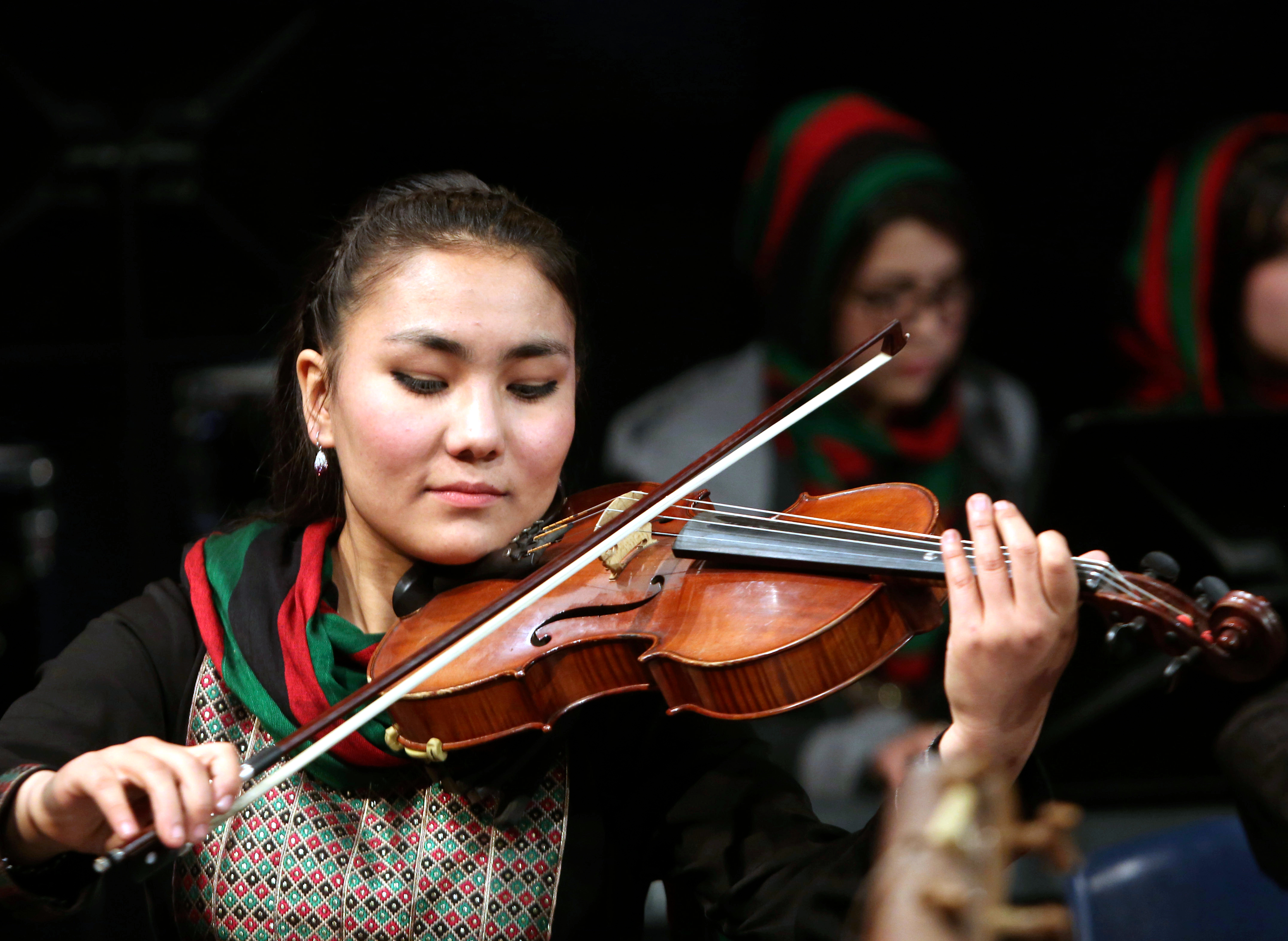 In this Wednesday, Feb. 15, 2017 file photo, Zarifa Adiba, 18, an orchestra conductor in Afghanistan, plays during a concert in Kabul. (AP Photo/Rahmat Gul)