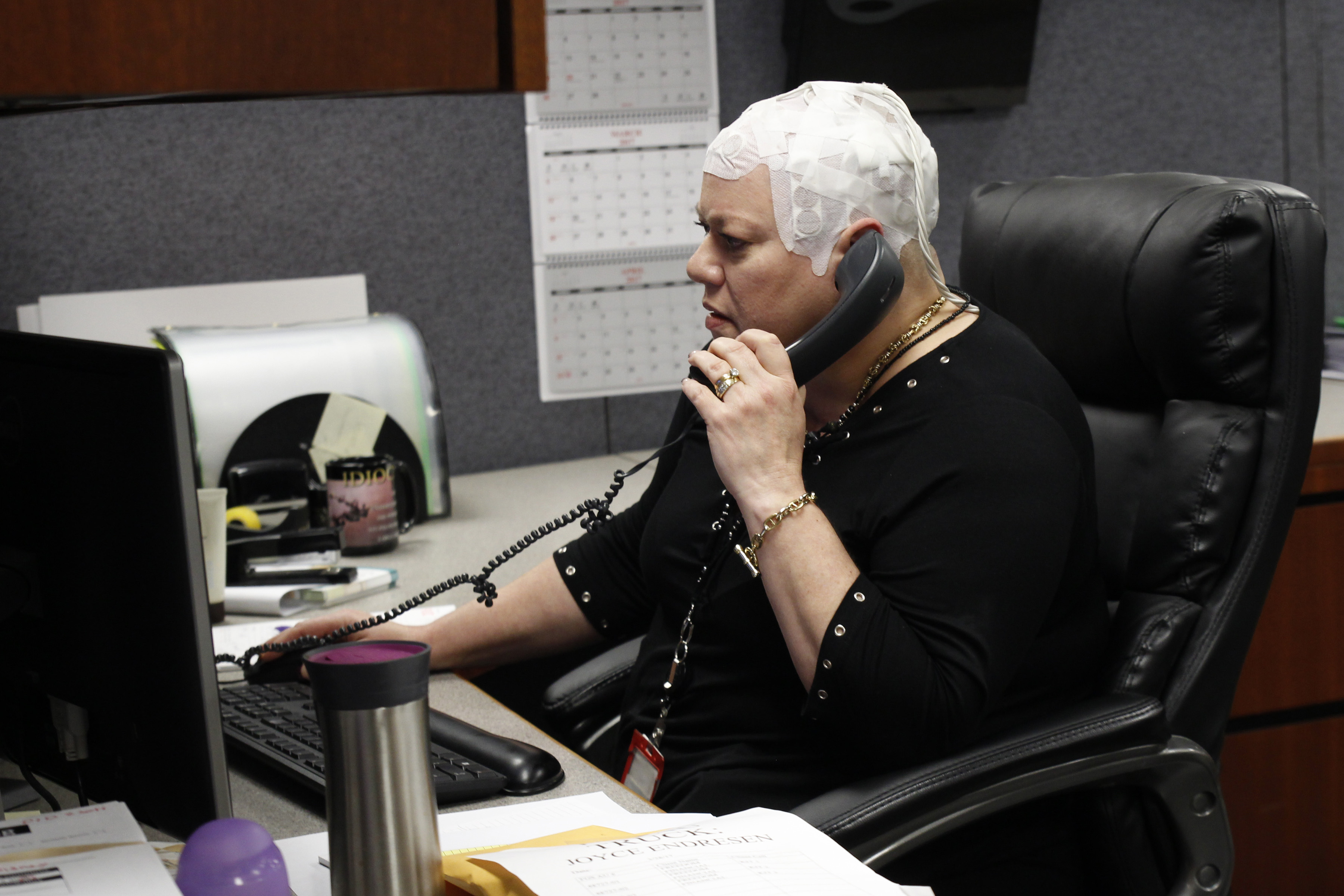 In this March 29, 2017 photo, Joyce Endresen wears an Optune therapy device for brain cancer, as she speaks on a phone at work in Aurora, Ill. (AP Photo/Carrie Antlfinger)