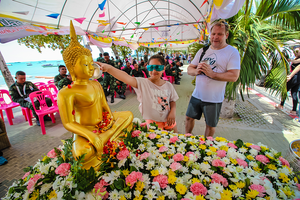 Respecting tradition and pouring scented water on the Buddha statue.