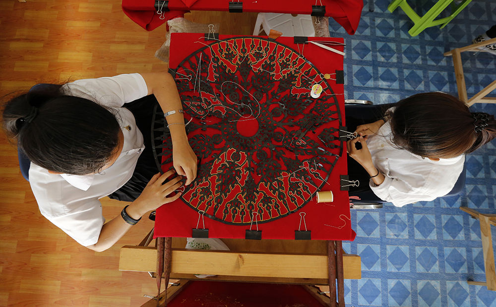 Women embroider intricate decorations for the royal crematorium. (AP Photo/Sakchai Lalit)
