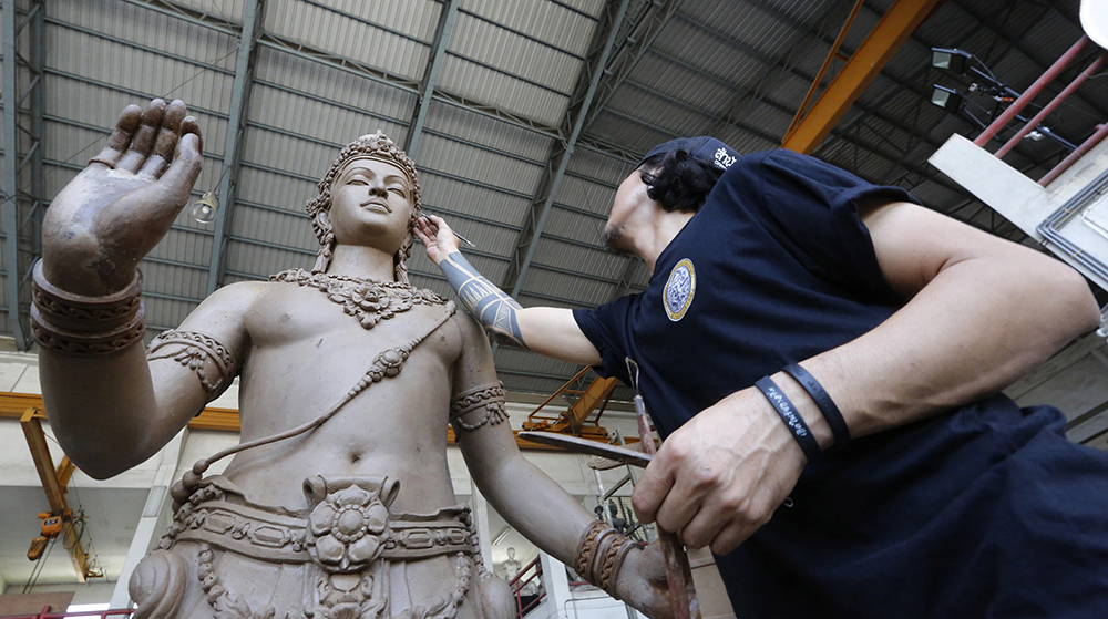 An artist sculpts deities and creatures from ancient Indian epics to decorate the royal crematorium. (AP Photo/Sakchai Lalit)