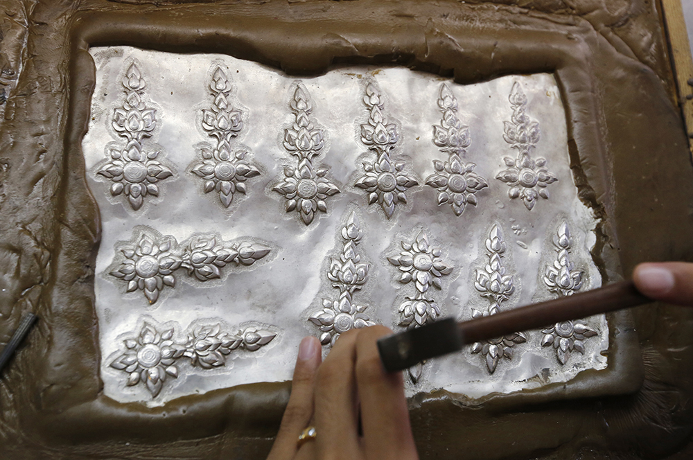 A student volunteer shapes designs on silver plates. (AP Photo/Sakchai Lalit)