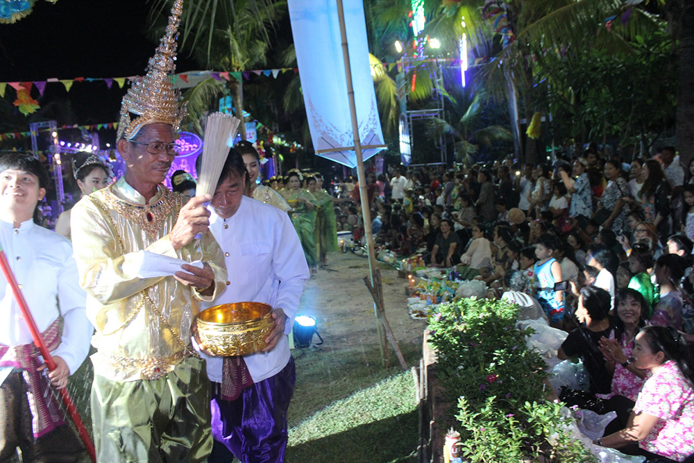 The witchdoctor or ceremony leader walks around and sprinkles water on the gathered masses before the food offering takes place.