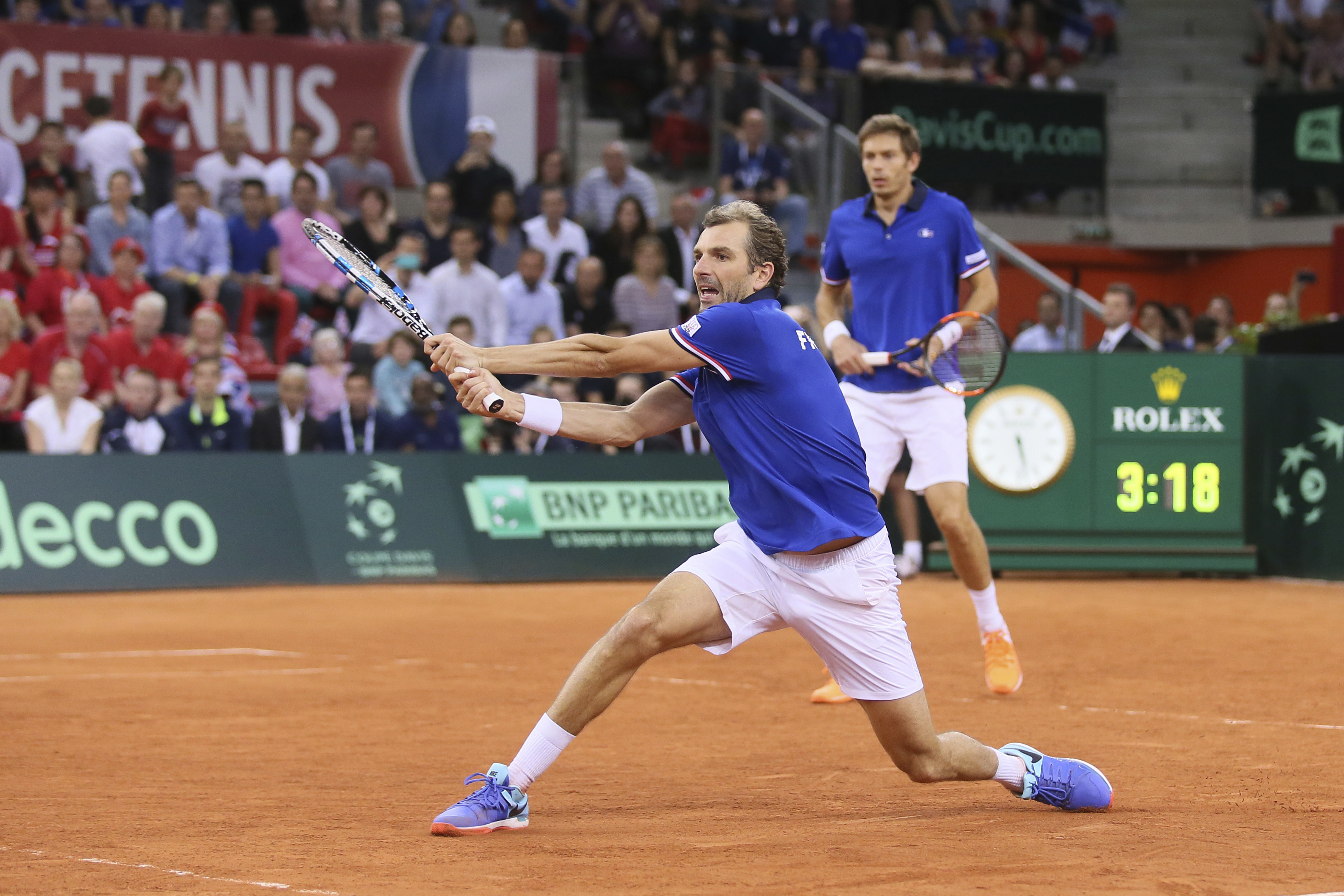 Julien Benneteau of France returns the ball to Jamie Murray and Dominic Inglot of Britain during their doubles Davis Cup quarterfinal tennis match at the Kindarena Stadium of Rouen, France, Saturday, April 8. France won the doubles and qualified for the semifinal. (AP Photo/David Vincent)