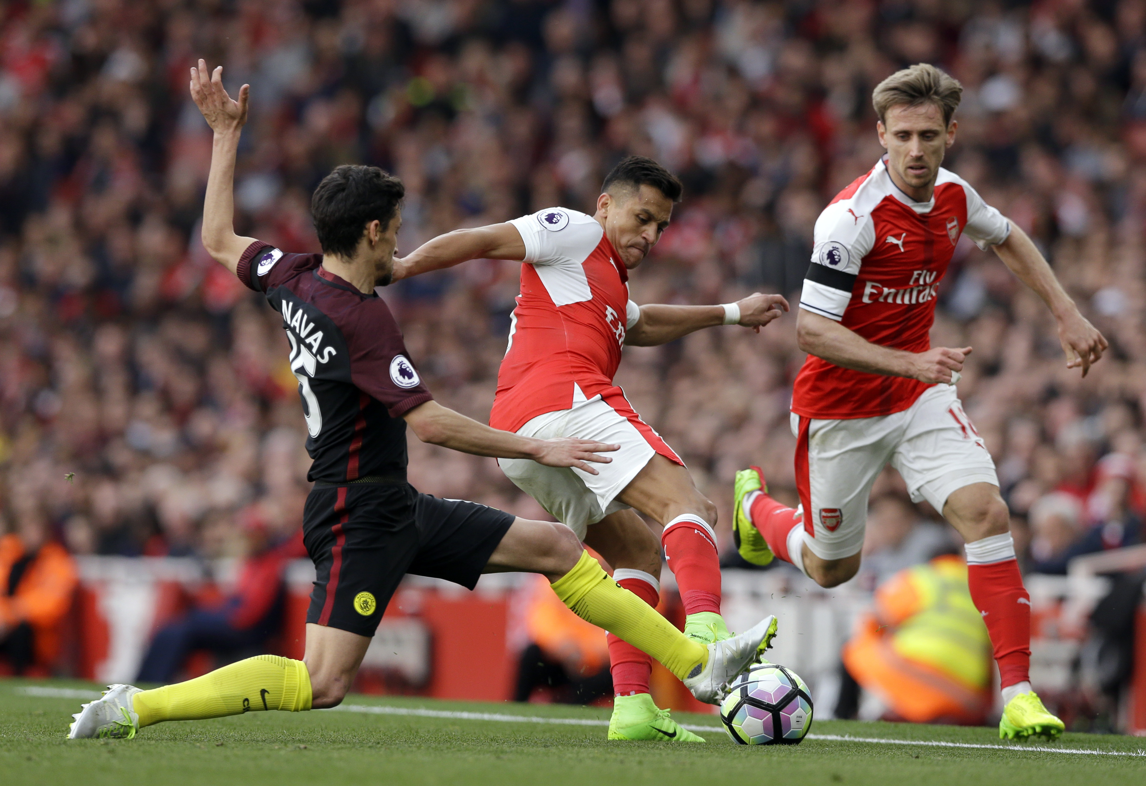 Manchester City's Jesus Navas, left, fights for the ball with Arsenal's Alexis Sanchez during their teams' English Premier League match at the Emirates stadium in London, Sunday, April 2. (AP Photo/Alastair Grant)
