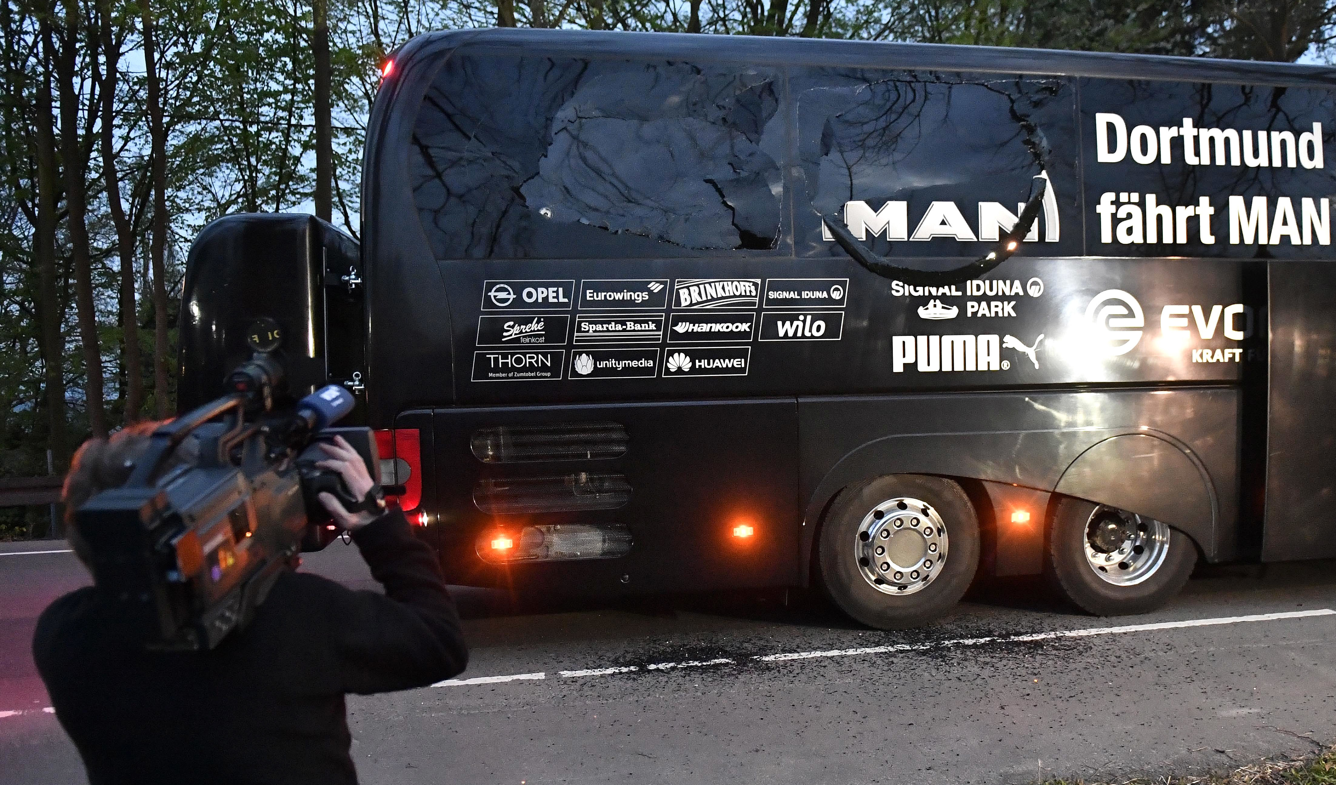 A camera man films Dortmund's team bus after it was damaged in an explosion before the Champions League quarterfinal between Borussia Dortmund and AS Monaco in Dortmund, western Germany, Tuesday, April 11. (AP Photo/Martin Meissner)