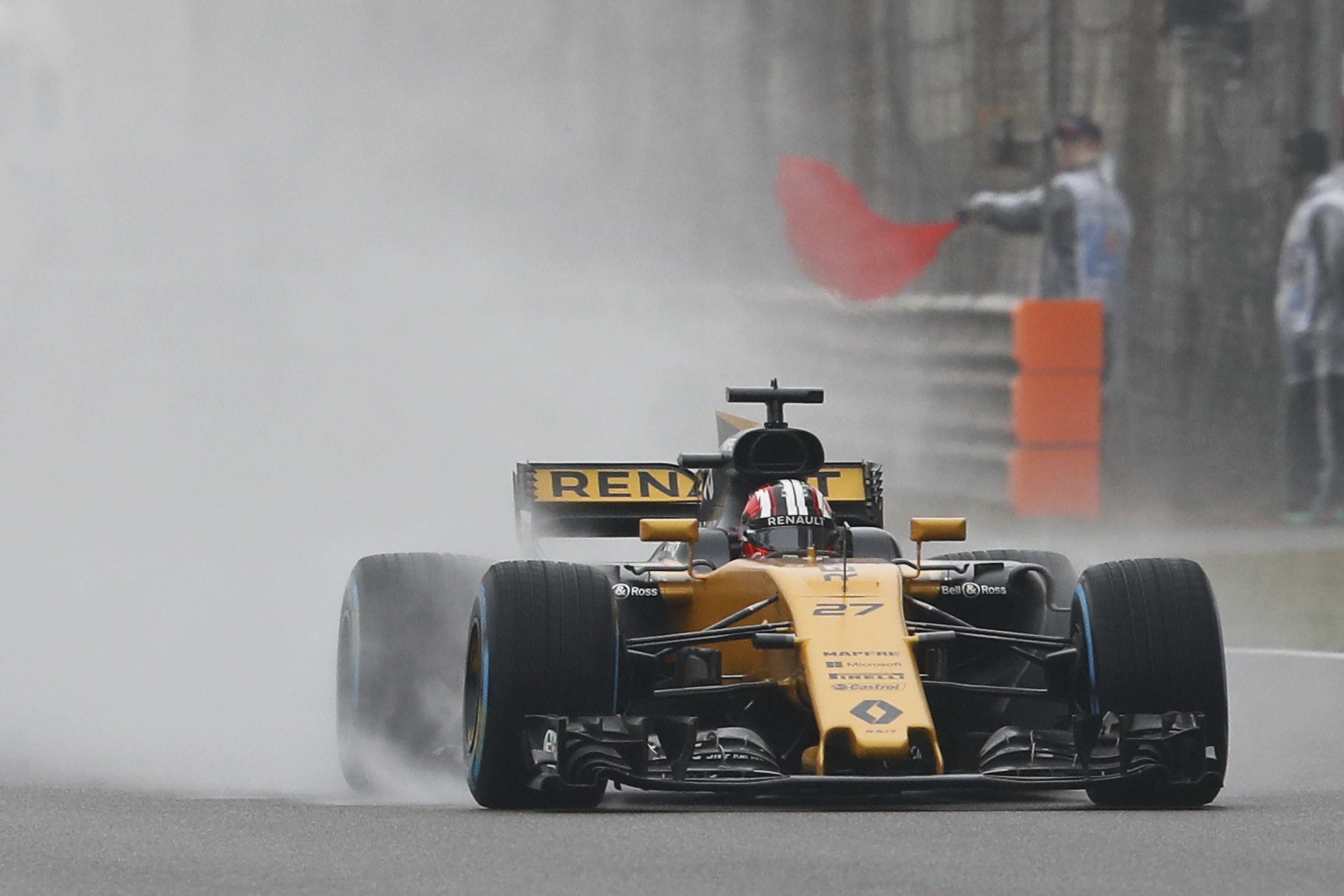 Renault driver Nico Hulkenberg of Germany steers his car past a track marshall waving a red flag during the first practice session for the Chinese Formula One Grand Prix in Shanghai, China, Friday, April 7. (AP Photo/Andy Wong)