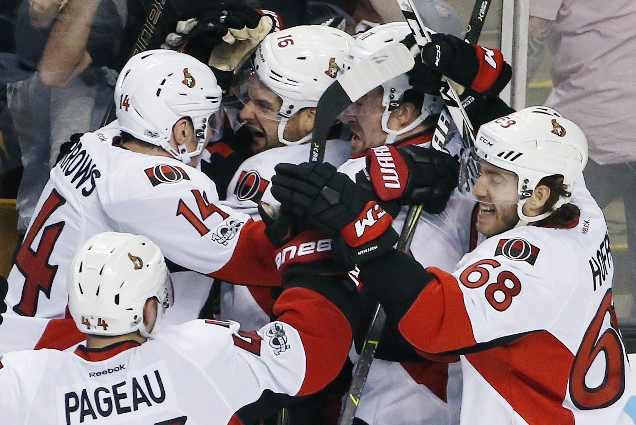 The Ottawa Senators including, Clarke MacArthur (16), Alex Burrows (14), Mike Hoffman (68) and Jean-Gabriel Pageau (44) celebrate after defeating the Boston Bruins 3-2 during overtime in game six of a first-round NHL hockey Stanley Cup playoff series, Sunday, April 23, 2017, in Boston. (AP Photo/Michael Dwyer)
