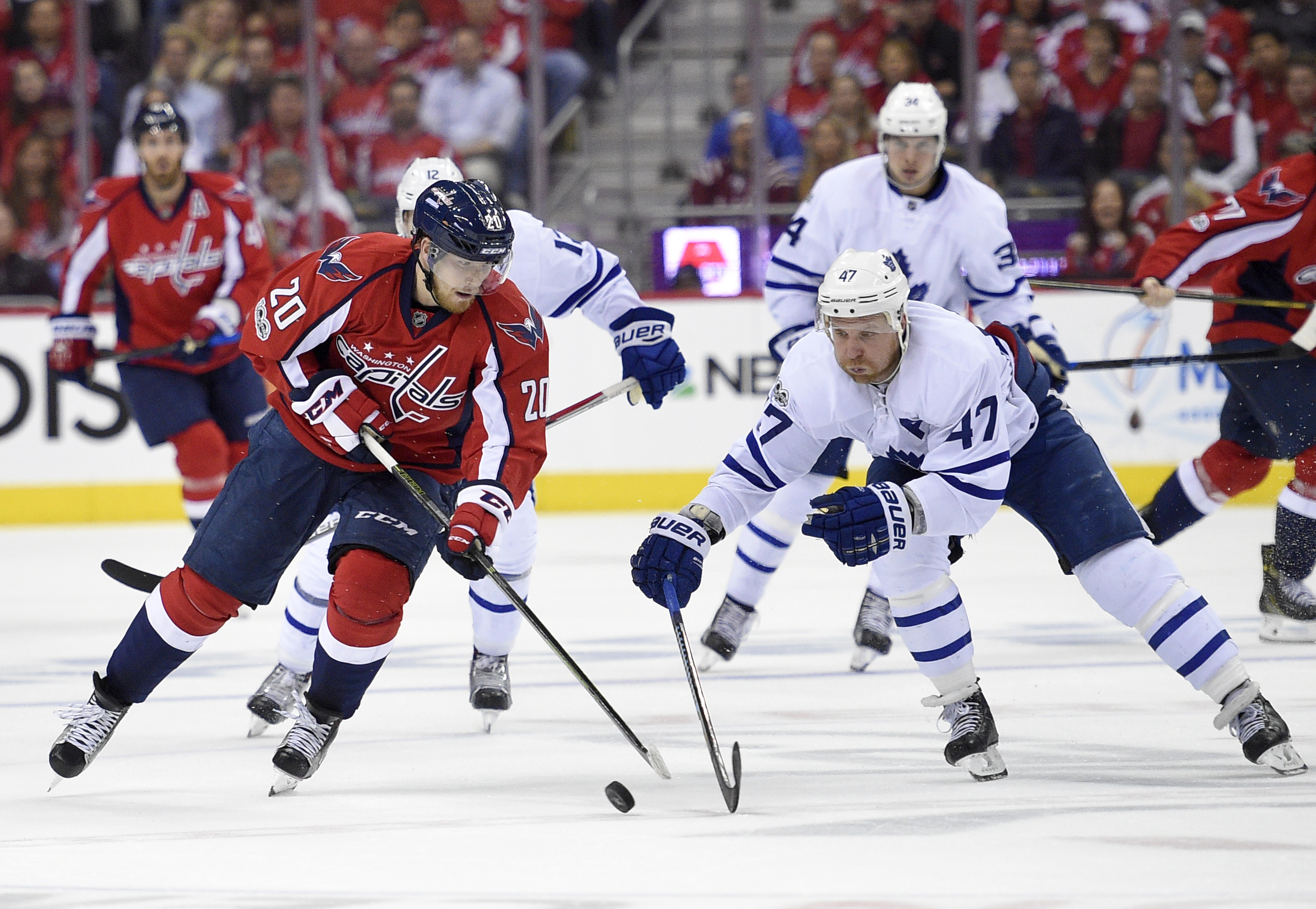 Washington Capitals center Lars Eller (20), of Denmark, battles for the puck with Toronto Maple Leafs center Leo Komarov (47), of Russia, during the second period of Game 5 in their NHL Stanley Cup hockey first-round playoff series, Friday, April 21, in Washington. (AP Photo/Nick Wass)