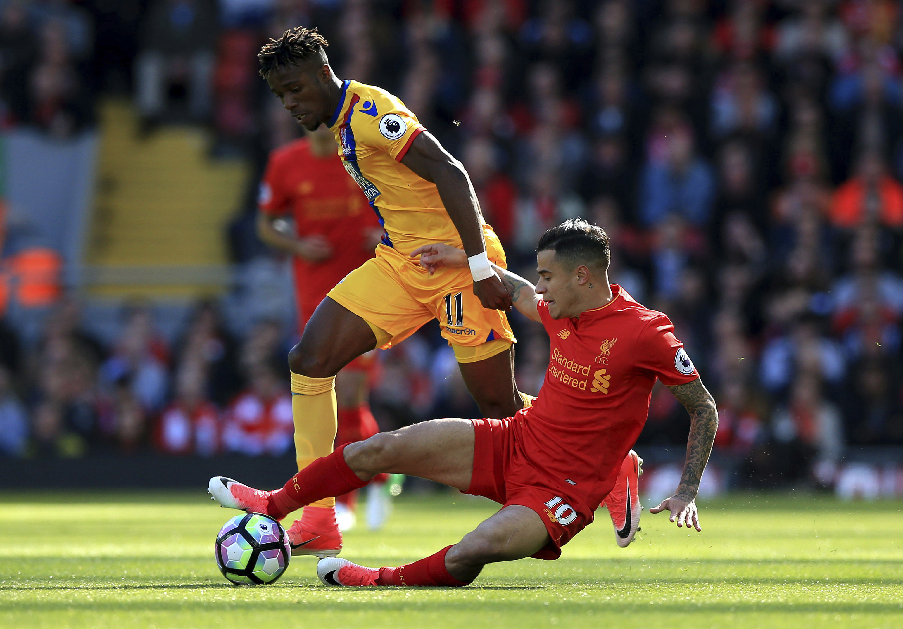 Crystal Palace's Wilfried Zaha, left, and Liverpool's Philippe Coutinho battle for the ball during the English Premier League soccer match against Crystal Palace at Anfield, Liverpool, Sunday April 23, 2017. (Peter Byrne/PA via AP)