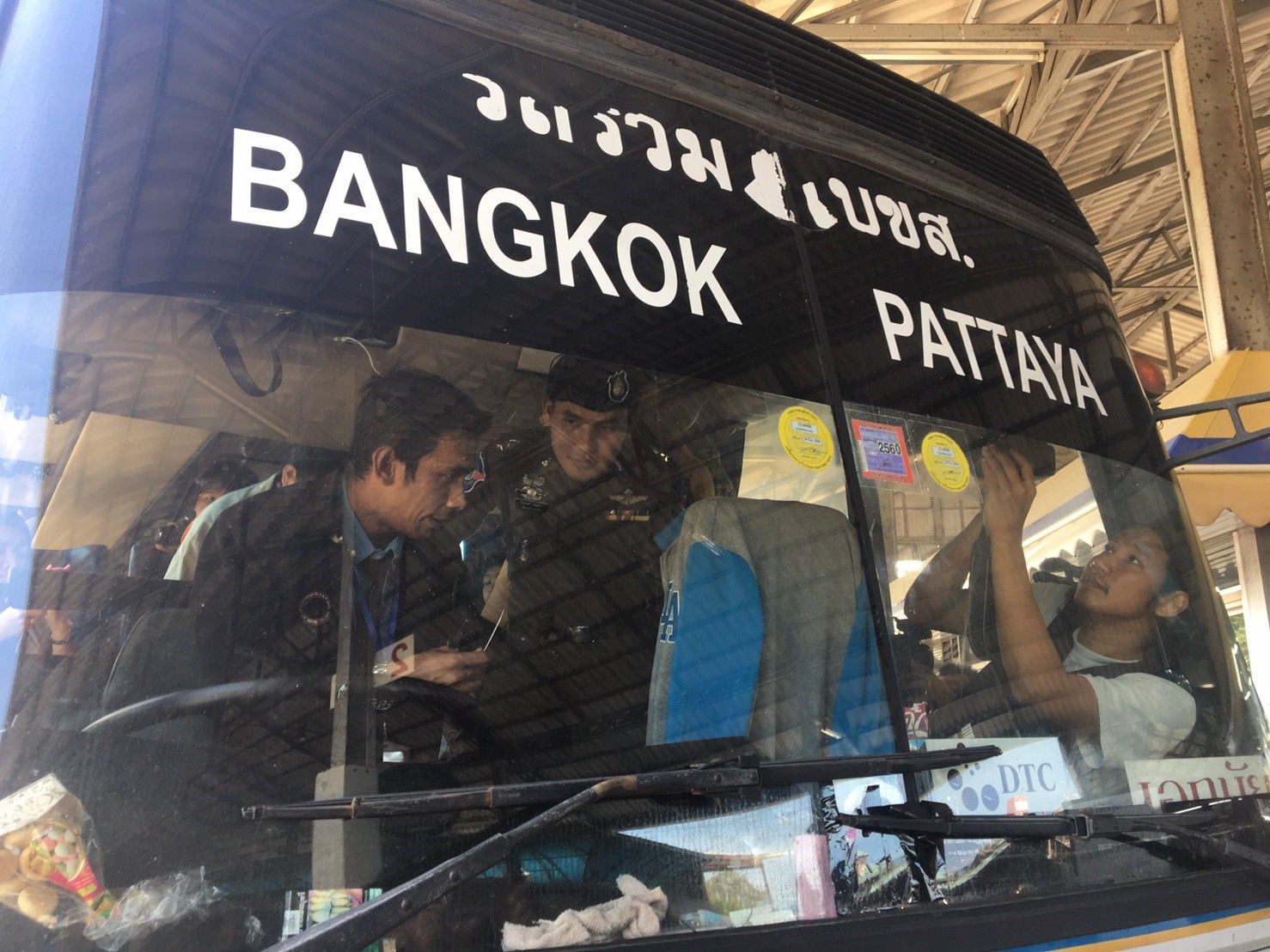 Police inspect a bus prior to it departing for Bangkok