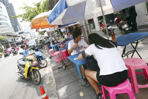 In this April 7, 2017 photo, people eat noodles at a street food shop during their lunch on Thonglor road in Bangkok, Thailand. (AP Photo/Sakchai Lalit)