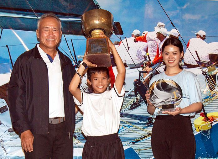 Panwa Boonnak (centre), winner of the 2017 Thailand Optimist National Championships at Ocean Marina Yacht Club in Pattaya, lifts the trophy aloft having been presented it by Admiral Kraisorn Chansuvanich (left), President of the Yacht Racing Association of Thailand. (Photo/Guy Nowell)