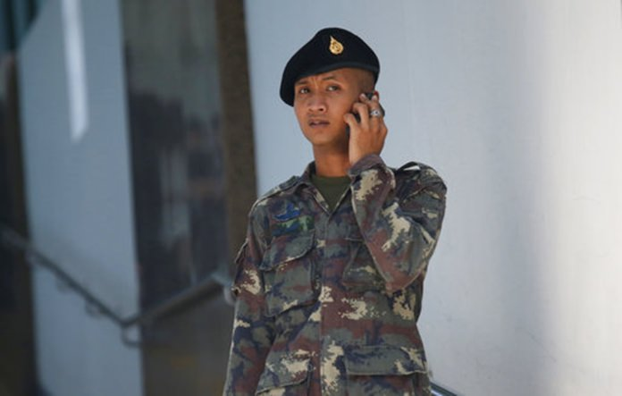A Thai soldier talks on his cell phone in front of the entrance of Phramongkutklao Hospital.(AP Photo/Sakchai Lalit)