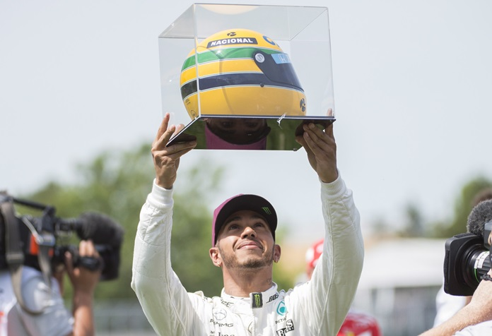 Mercedes driver Lewis Hamilton, of Great Britain, holds up a racing helmet of former F1 driver Ayrton Senna after winning pole position at the F1 Canadian Grand Prix auto race, Saturday, June 10, in Montreal. (Graham Hughes/The Canadian Press via AP)