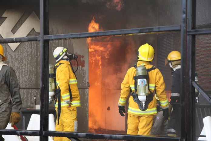 Firefighters attempt to gain entry through a service entrance as fire rages just inside. Thanks to Wanchai Pingate's quick thinking, employees trapped inside the building were able to escape with minor injuries.