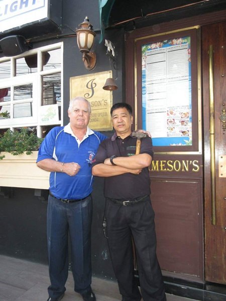 Wanchai Pingate holds the hammer he used to break open the door and free the victims trapped inside, as Kim Fletcher, landlord of Jameson's Irish Pub, congratulates him for his heroic effort.