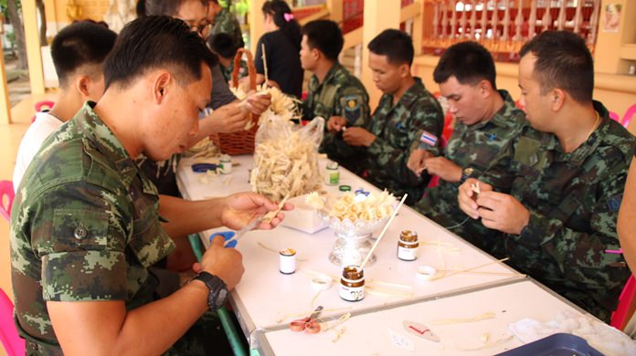 Military officers teach teenagers (not shown) caught using drugs how to make artificial flowers for HM the late King's funeral.