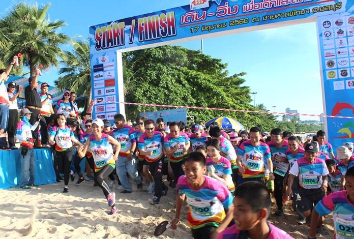 Athletes burst through the tape at the start of the YWCA walk-run event at Pattaya Beach, Saturday, June 17.