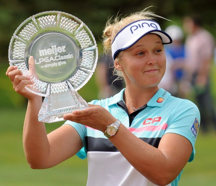 Brooke Henderson, of Canada, poses with the trophy after winning the Meijer LPGA Classic golf tournament at Blythefield Country Club. Sunday, June 18, in Grand Rapids, Mich.. (Cory Olsen/The Grand Rapids Press via AP)