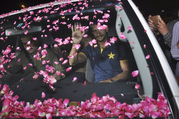 Pakistani cricketer Hasan Ali waves to fans who showered rose petals on his car at Lahore airport in Pakistan, Tuesday, June 20. (AP Photo/K.M. Chaudary)