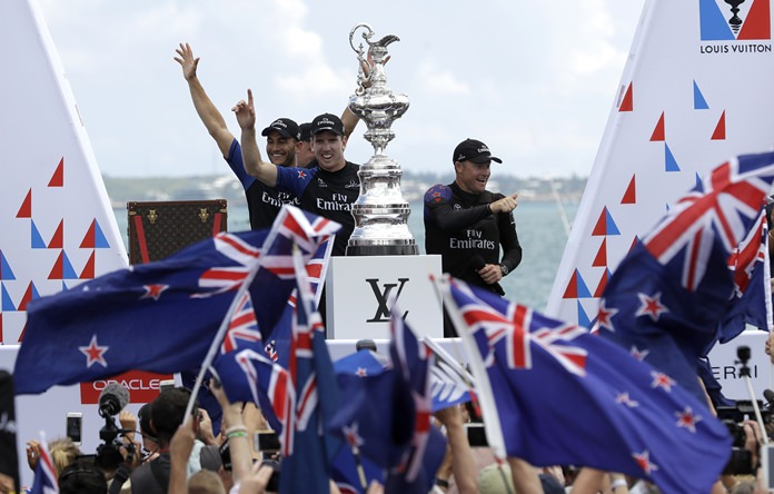Emirates Team New Zealand helmsman Peter Burling and Glenn Ashby, right, celebrate with teammates after winning the America's Cup, Monday, June 26, in Hamilton, Bermuda. (AP Photo/Gregory Bull)