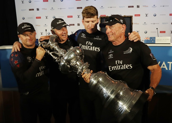 Emirates Team New Zealand members from left, skipper Glenn Ashby, Matteo De Nora, helmsman Peter Burling, left, and team boss Grant Dalton hold the America's Cup trophy after their press conference following their win over Oracle Team USA, Monday, June 26, 2017,in Hamilton, Bermuda. (AP Photo/Gregory Bull)