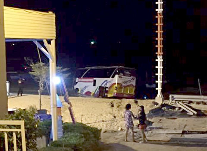 Bystanders look on as rescue workers attempt to recover a tour bus which crashed into the sea in north Pattaya on Tuesday evening.